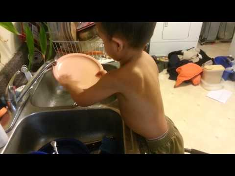 Three year old boy washes dishes without permission
